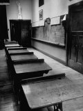 Looking Down Row of Empty Scarred Old Fashioned Desks in Schoolroom