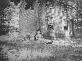 Miss Colwell Sitting Against Two Trees by a Small House