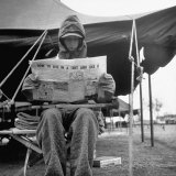 Hooded Recruit Wearing Oddly Assorted Clothing Issue and Reading Copy of the Base Newspaper