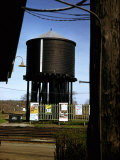 Photo Taken from Window of a Train Showing Water Storage Tower Beside Tracks