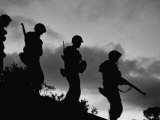 Four Soldiers with Helmets and Rifles Moving on Crest of Ridge  on Patrol at Night