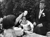 Flower Girl Janet Auchincloss Holding Up a Wedge of Wedding Cake for Bridegroom Sen John Kennedy