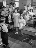 Children Reciting the Pledge of Allegiance as a Boy Holds the Us Flag in their Classroom