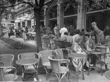 People Eating at a Sidewalk Cafe Next to the Excelsior Hotel