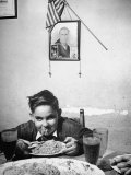 Boy Eating Spaghetti under Picture of His Brother Who Died During Invasion of Sicily