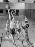 Five Young Boys Wearing Gym Clothes and Playing a Game of Basketball in the School Gym