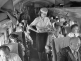 Eastern Airline Travelers Receiving a Mid-Flight Meal from a Female Steward