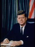 Pres John F Kennedy Sitting at His Desk  with Flag in Bkgrd