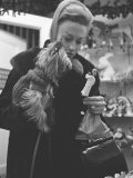 Shopper Looking at Tiny Figurine as She Holds Her Yorkshire Terrier in Arms at Saks Fifth Avenue