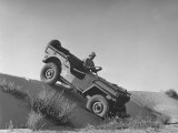 US Army Jeep Rolling Down a Sand Dune During Training Maneuvers in the Desert