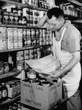 Grocer Re-Stocking Food in His Store