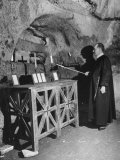 Priest Lighting a Candle in Catacombs in Rome