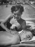 Major Kenneth Trout Having His Shoulders Rubbed with Sunblock by His Wife Ella Raines
