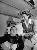 An Airline Stewardess Adjusting a Pillow for a Sailor on Leave