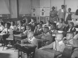 Children Sitting at their Desks in a Classroom  Teachers at the Rear of the Room