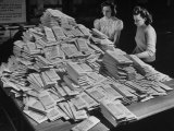 Two Girls Looking over Huge Pile of Policies Waiting to Be Mailed