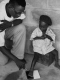 Doctor Pulling Parasite Guinea Worm from Foot of Little Boy