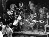 People Patronizing a Tea Shop on Market Day