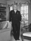 Broker Charles E Merrill Standing in Living Room with Hand Resting on Chair