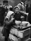 Pair of Russian Children Having a Meal of Molasses Bread and Coffee in a Displaced Persons Camp