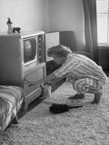 Young Woman Attending to Her Housework by Dusting Off Her Television Set