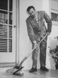 Man Using Combination Shovel and Brush to Clean Porch