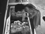 Woman Reaching Further into the Home Freezer and Pulling Packages of Frozen Vegetables