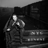 Itinerant Man  Aka a Hobo  Sitting Atop a Freight Car with His &quot;Bindle&quot;
