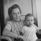 Close-Up of Woman Sitting with Baby Daughter Aboard Ship