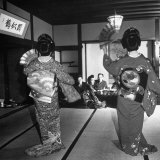Two Geishas Dancing with Fans on Stage as Guests and Other Geshias Watch from Dinner Table