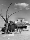 Two Boys Playing Nr a Dead Tree as Judge Roy Langrty and a Man Walk Past a General Store