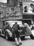 Men Pushing a Car Up a Street  Bilboards Overhead