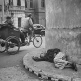 Staving Beggar Boy Sleeping While a Rickshaw Speeds on by Him