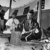 Japanese Swordmaker Making a Samarai Sword as Shinto Priest Looks On