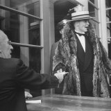 Student in Racoon Coat and Straw Hat Giving Ticket to Man at Door  at the Charleston Party