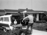 Baseball Player Mickey Mantle Loading Trunk into His Car as Son Danny Observes