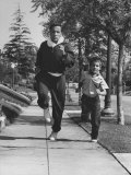 Tennis Player Pancho Segura Running with His Younger Son