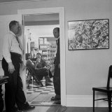 Painter Jackson Pollock Standing in Doorway Near One of His Paintings