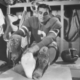 Football Player Ben Agajanian Putting on Football Cleats