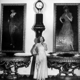 Actress Marion Davies  Standing under Two Portraits at Home