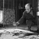 Painter Jackson Pollock Squatting on Floor  Applying Sand to Canvas  in Long Island