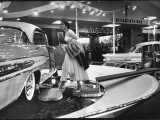 Model Gingerly Traversing Stepping Stones to Get to La Parisienne Pontiac Hard Top Car on Display