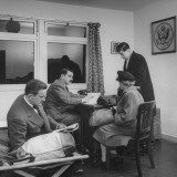 Business Men at US Consul in Airport Talking with Woman