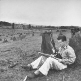 Artist Carl Hall Sitting in a Field and Sketching