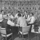 Seven Men Sitting around Table Playing Poker