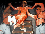 Actress Sandra Bernhard Lifted by Men From Stacked Louis Vuitton Trunks at Centennial Party