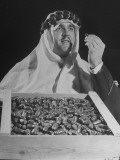 Man Dressed in Arabic Clothing Holding Crate of Dates During Date Festival