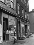 Tom Is Your Barber Shop with Classic Candy-Striped Barber Pole Next to its Entrance