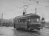 A Passenger-Filled Streetcar Traveling Through a Bomb-Damaged City