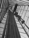 Vertical View of Oil Rig Showing Stacked Drill Pipes and Derrick Man at Work